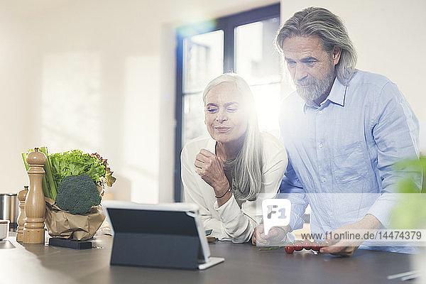 Glückliches älteres Ehepaar bereitet mit Online-Rezept in der Küche Essen zu