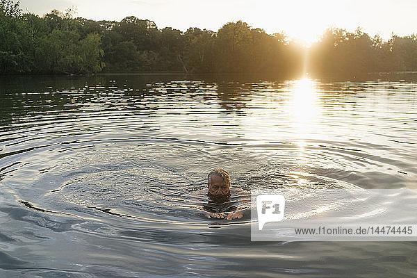 Älterer Mann schwimmt bei Sonnenuntergang in einem See