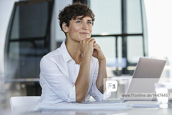 Lächelnde Geschäftsfrau sitzt mit Laptop am Schreibtisch im Büro