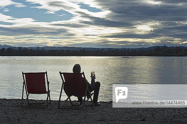 Deutschland  Mann sitzt mit einem Glas Bier am Ufer des Ammersees und betrachtet den Sonnenuntergang