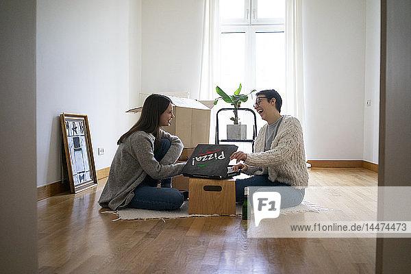 Junge Frauen sitzen auf dem Boden ihres neuen Hauses und essen Pizza