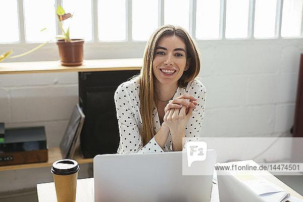 Porträt einer lächelnden jungen Frau am Schreibtisch im Büro
