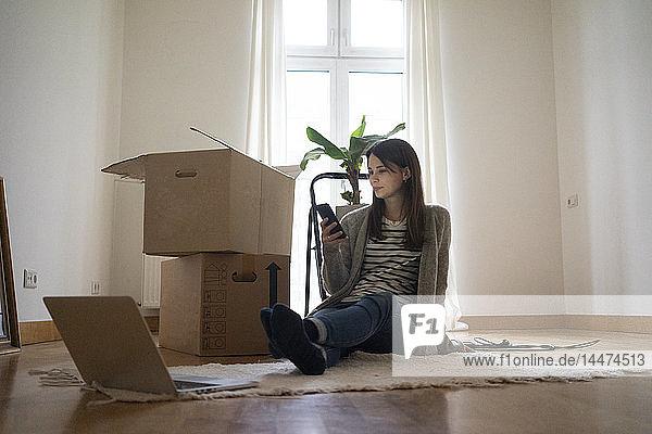 Junge Frau sitzt auf dem Boden ihres neuen Hauses und benutzt ein Smartphone