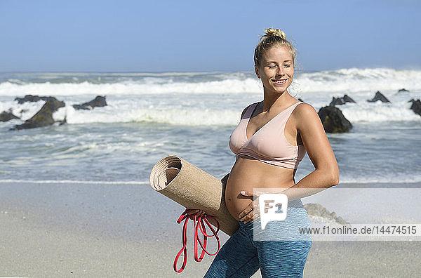 Aktive schwangere Frau hält Gymnastikmatte am Strand