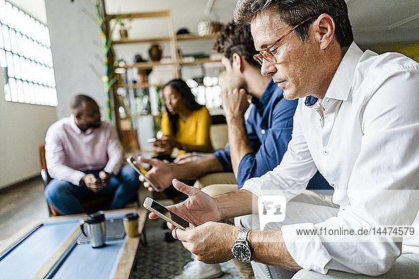 Geschäftsteam sitzt im Loft-Büro und benutzt Mobiltelefone