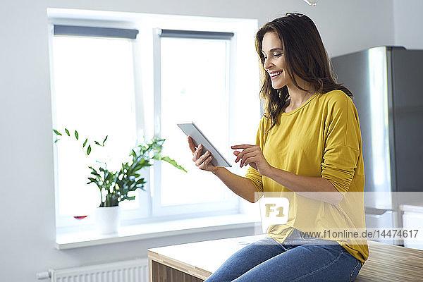 Frau sitzt zu Hause auf dem Küchentisch und benutzt ein digitales Tablet