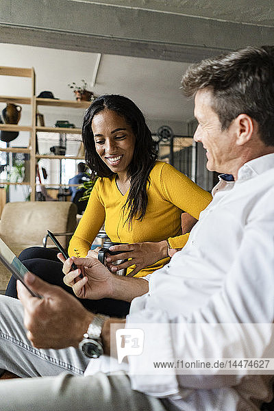 Smiling businesswoman and businessman using tablet on sofa in loft office