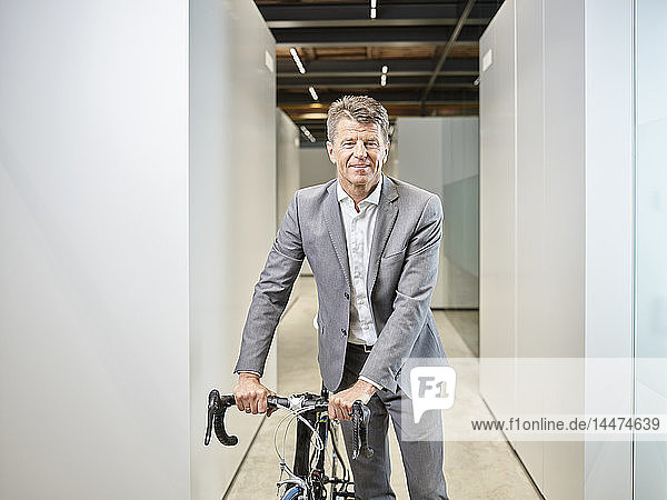 Portrait of smiling businessman with bicycle on office floor