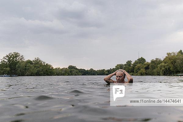 Älterer Mann schwimmt in einem See