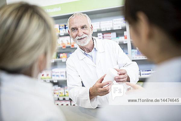 Apothekerin lächelt zwei Frauen in der Apotheke an