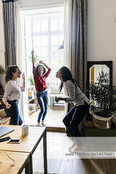 Three women at home having a party and dancing