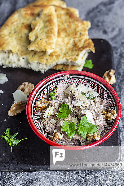 Bowl of homemade aubergine cream with walnuts  parmesan and parsley served with pita bread