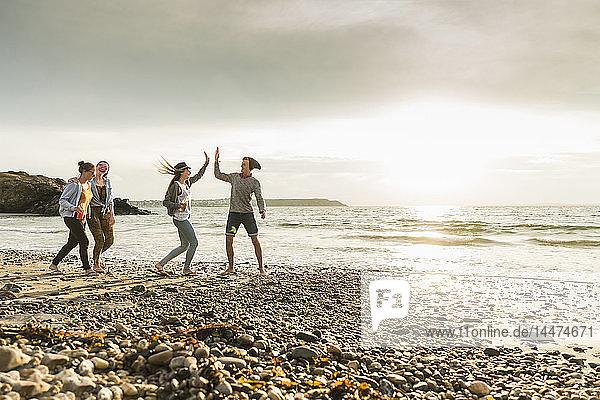 Glückliche Freunde beim Spaziergang am Strand bei Sonnenuntergang