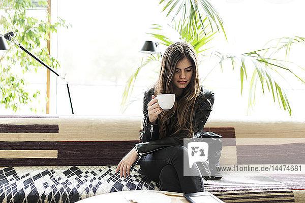 Junge Frau sitzt in einem Café und trinkt Kaffee