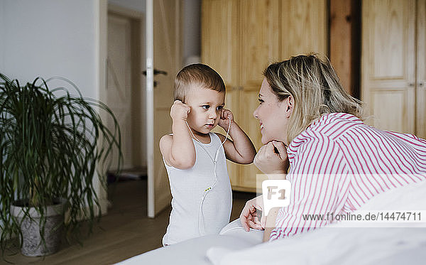 Smiling mother watching toddler son using earphones in bedroom at home