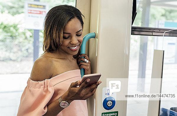 Großbritannien  London  lächelnde schöne Frau mit Handy im Zug