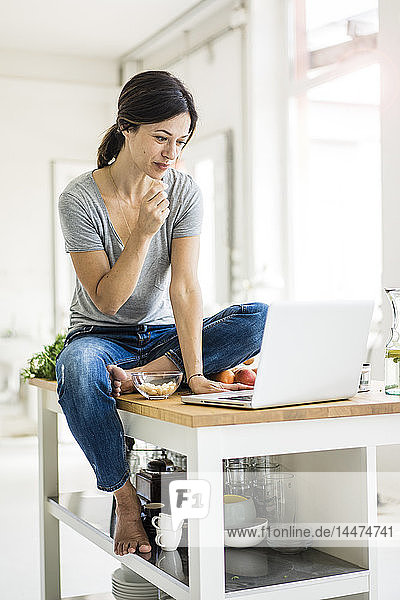 Woman sitting on kitchen table  searching for healthy recipes  using laptop