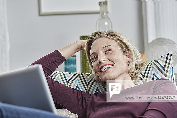 Smiling young woman with tablet lying on couch at home