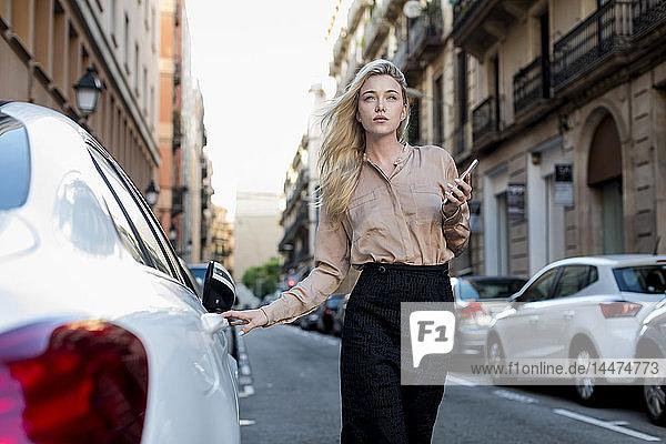 Junge Geschäftsfrau mit Handy auf Stadtstraße