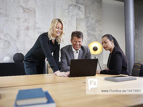 Geschäftsmann und zwei Geschäftsfrauen teilen sich einen Laptop in einem modernen Büro