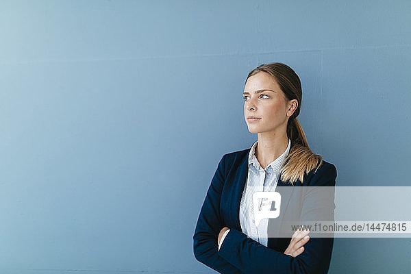 Porträt einer jungen Geschäftsfrau vor blauem Hintergrund  die skeptisch schaut