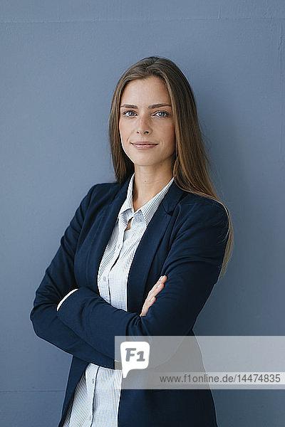 Porträt einer jungen Geschäftsfrau vor blauem Hintergrund  mit verschränkten Armen