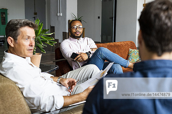Businessmen discussing documents on sofa in loft office
