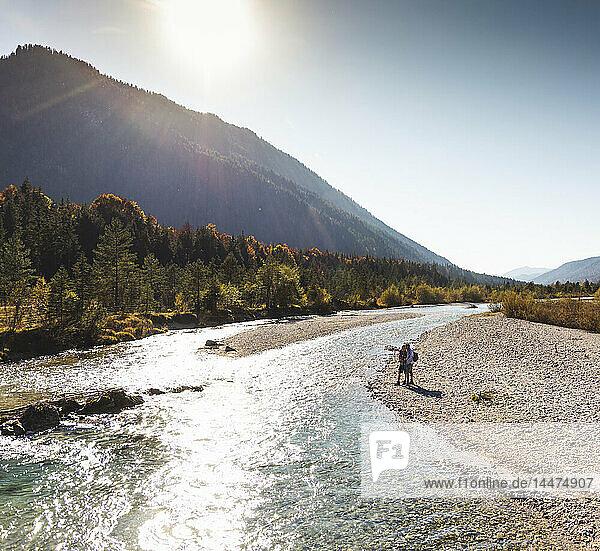 Österreich  Alpen  Ehepaar auf Wanderung an einem Bach stehend
