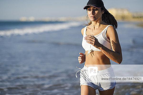 Sportive woman running on the beach