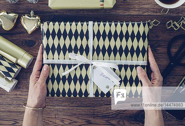 Frauenhände halten verpacktes Geschenk  Draufsicht