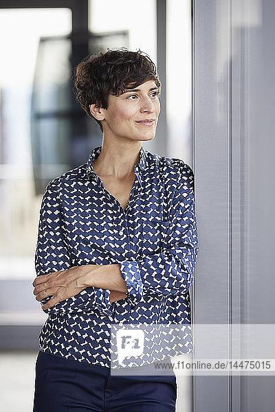 Lächelnde Geschäftsfrau im Büro schaut aus dem Fenster