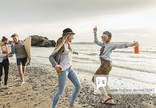 Glückliche Freunde mit Surfbrett und Getränken am steinigen Strand spazieren