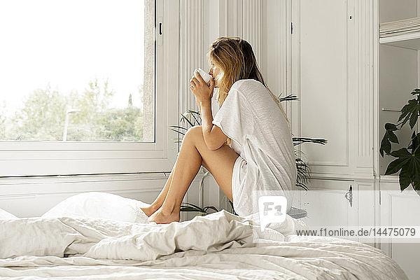 Junge Frau sitzt im Bett und trinkt Kaffee