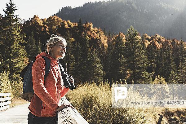 Österreich  Alpen  Frau auf einer Wanderung auf einer Brücke stehend mit Fernglas