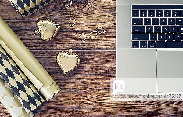 Büroschreibtisch mit Laptop  Geschenkpapier  Büroklammer und goldenen Weihnachtskugeln