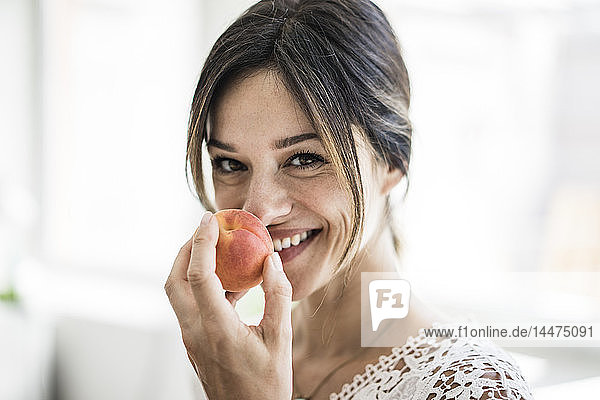 Laughing woman smelling an apricot