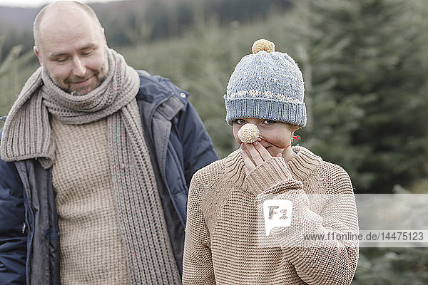 Playful boy with his father on a Christmas tree plantation