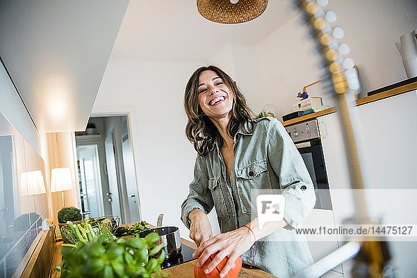 Laughing woman slicing pumpkin in her kitchen