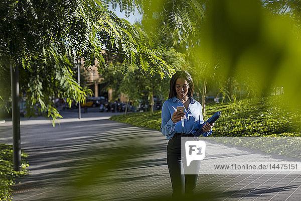 Geschäftsfrau benutzt Smartphone  hält Laptoptasche im Park