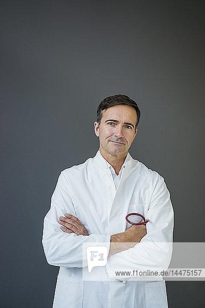 Porträt eines selbstbewussten Arztes  der an einer grauen Wand steht