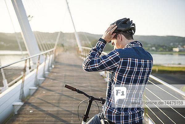 Junger Mann auf Fahrrad  der auf einer Brücke einen Helm aufsetzt