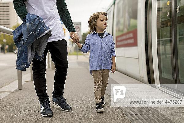 Vater und Sohn gehen Hand in Hand an der Straßenbahnhaltestelle in der Stadt