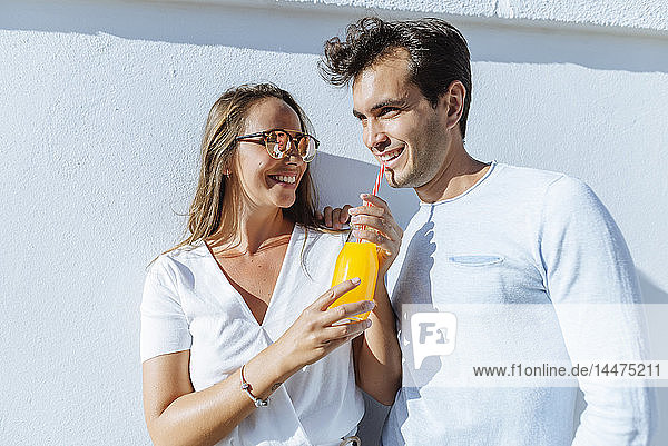 Glückliches Paar  das sich an einem sonnigen Tag einen Orangensaft teilt