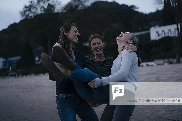 Deutschland,  Hamburg,  sorgenfreie Mutter mit zwei jugendlichen Mädchen abends am Strand am Elbufer