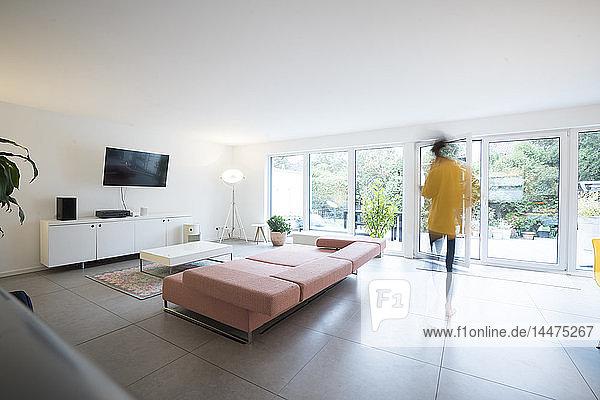 Frau bewegt sich in einem geräumigen Wohnzimmer zu Hause