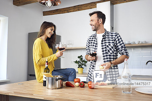 Affectionate couple in kitchen  preparing spaghetti toghether  drinking red wein