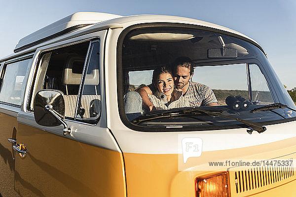 liebevolles Paar  das in seinem Wohnwagen sitzt  die Arme um sich legt und den Sonnenuntergang betrachtet
