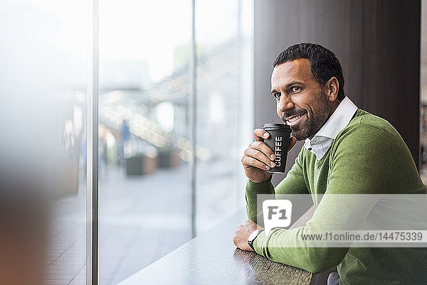 Businessman with coffee to go in a cafe