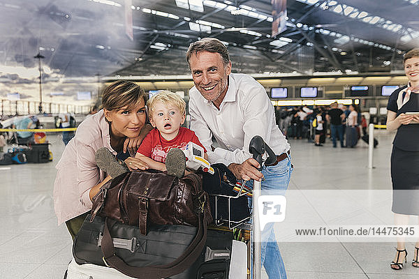 Portrait of happy family with baggage cart at the airport