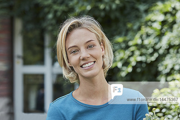 Portrait of smiling woman in garden of her home